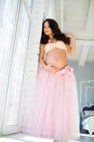 站立在薄纱裙子的一个窗口附近的美丽的怀孕的女孩 免版税库存照片