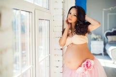 站立在薄纱裙子的一个窗口附近的美丽的怀孕的女孩 图库摄影