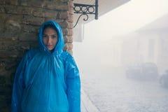 站立在薄雾的蓝色雨衣的年轻时尚妇女户外 老房子的砖墙 摊铺机 雨毛毛雨  库存图片