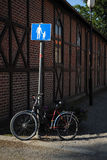 站立在行人穿越道标志旁边的自行车 库存图片