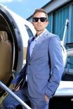 站立在行政喷气机的门的衣服的年轻人 免版税库存照片