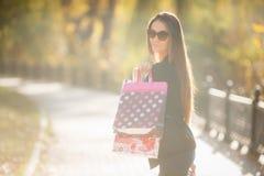 站立在街道上的一名美丽的愉快的妇女的画象举行购物袋微笑 库存图片