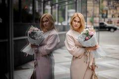 站立在街道上的女孩拿着美丽的花束 库存照片