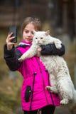 站立在街道上的小女孩采取与一只离群猫的一selfie 爱 库存图片