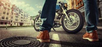 站立在街道上的摩托车附近的骑自行车的人 免版税库存照片