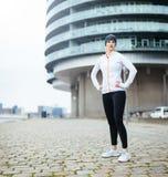 站立在街道上的运动服的适合的少妇 库存照片