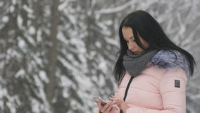 站立在街道上的年轻美丽的女孩和为聊天使用她的电话 影视素材