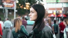 站立在街道上的年轻美丽的妇女 浅黑肤色的男人轮和看对照相机 慢的行动 股票视频