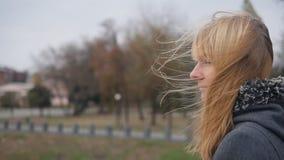 站立在街道和她的头发上的女孩振翼在风 慢动作录影镜头 影视素材