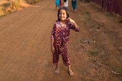 站立在街道和调查照相机的柬埔寨人地方女孩 免版税库存图片