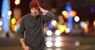 站立在街道旁边的性感的都市行家在晚上 免版税库存照片