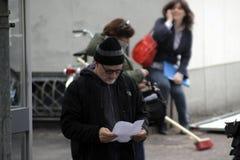 站立在街道读书的大卫・芬奇 免版税图库摄影