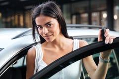 站立在被打开的汽车附近的美丽的少妇户外 免版税库存照片