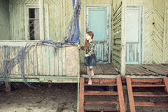 站立在被放弃的木房子台阶的逗人喜爱的小女孩  免版税库存照片
