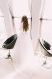 站立在被日光照射了窗口旁边的丝绸白色礼服的美丽的新娘在两把现代椅子附近 库存图片