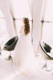 站立在被日光照射了窗口旁边的丝绸白色礼服的美丽的新娘在两把现代椅子附近 免版税库存图片