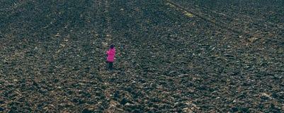 站立在被犁的领域中间的女孩 免版税库存图片