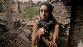 站立在被破坏的砖瓦房附近和看照相机的hijab的年轻回教妇女,哀伤和沮丧 股票录像