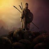 站立在装甲的传奇战士拿着他的武器 免版税库存图片