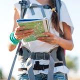 站立在观看在地图的山的峰顶的年轻运动的妇女 库存照片