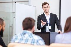 站立在论坛的快乐的报告人在会场里 免版税库存图片