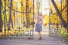 站立在词条门附近的愉快的妇女对公园在秋天 免版税库存图片