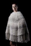 佩带温暖的白色的秀丽女性模型编织了雨披 免版税库存图片