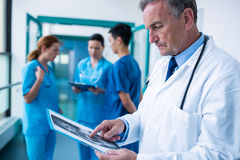 站立在走廊审查的X-射线的医生 免版税库存照片