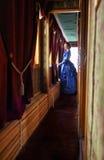 站立在走廊的蓝色葡萄酒礼服的少妇减速火箭 库存图片