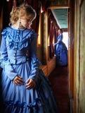 站立在走廊的蓝色葡萄酒礼服的少妇减速火箭 免版税库存照片