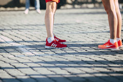 站立在跑鞋耐克的女孩前面的爱迪达跑鞋的年轻人 图库摄影