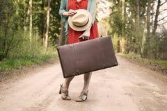 站立在路中间的礼服和葡萄酒手提箱的妇女 库存图片