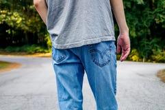 站立在路的一把叉子的青少年的男孩 免版税库存照片