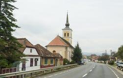 站立在路的圣尼古拉斯教会穿过Bunesti村庄在罗马尼亚 免版税库存图片
