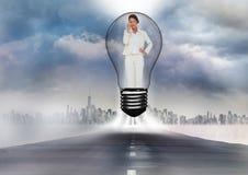 站立在路的电灯泡的女实业家的数字式综合图象反对都市风景 图库摄影