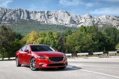 站立在路的红色汽车在山附近在白天 免版税库存图片