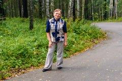 站立在路的长裤和玻璃的60岁的妇女在充分的成长的公园 免版税库存图片