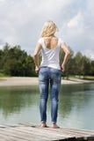 站立在跳船的白肤金发的妇女 免版税库存照片