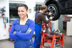 站立在车库的女性技工 免版税库存图片