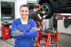 站立在车库的女性技工 库存图片