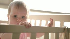 站立在轻便小床的逗人喜爱的婴孩 逗人喜爱的童年 小儿床的小孩女孩 股票录像
