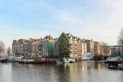 站立在运河的银行的议院在阿姆斯特丹 免版税库存图片