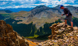 站立在远足地形的落矶山探险边缘 免版税图库摄影