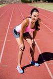 站立在连续轨道的疲乏的女运动员画象  免版税库存照片
