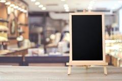 站立在迷离咖啡馆的桌上的空白的黑板与bokeh bac 免版税库存图片