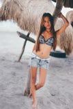 站立在遮光罩伞的海滩的性感的女孩 免版税库存图片