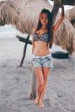 站立在遮光罩伞的海滩的性感的女孩 库存照片