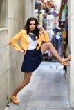 站立在都市背景中的年轻深色的妇女 图库摄影
