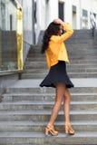 站立在都市背景中的年轻深色的妇女 库存照片