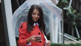 站立在都市街道上和使用智能手机的愉快的年轻企业夫人佩带在红色外套 拿着在她的她伞 股票视频